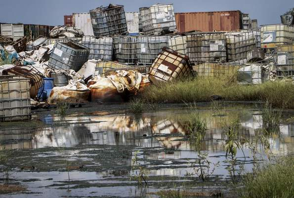 In this photo taken Monday, Oct. 1, 2018, containers used for hazardous chemicals lie exposed and piled up at a junkyard run by the Chinese-led Dar Petroleum Operating Company in Gumry, near Paloch, in South Sudan. (AP Photo/Sam Mednick)