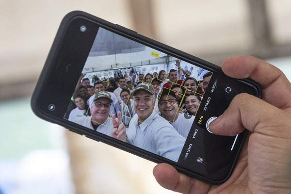 In this Jan. 29, 2020 photo, Colombia's President Ivan Duque, center, takes a selfie with Howard Buffet, left, and cocoa farmers, in La Gabarra, Colombia, Wednesday. (AP Photo/Ivan Valencia)