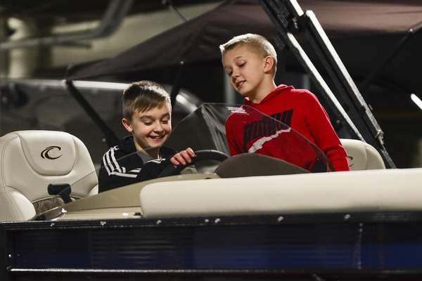 RIGHT: Zeb Campbell, 11, left dreams of warmer weather Thursday while pretending to pilot a boat with his mate Austin Parteko, 10, during the annual event.