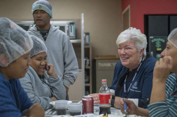 Associated Press photos In a photo provided by Tyson Foods, Karen Diefendorf, right, director of Chaplain Services at Tyson, talks with employees at the company's poultry plant in Springdale, Arkansas, in October 2018.