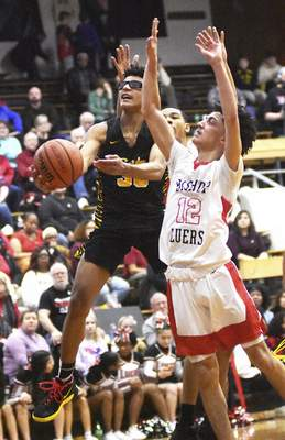 Katie Fyfe | The Journal Gazette  Snider sophomore Karson Jenkins goes to take a shot while Bishop Luers senior Landon Moore tries to stop him during the second quarter at Bishop Luers High School on Friday.