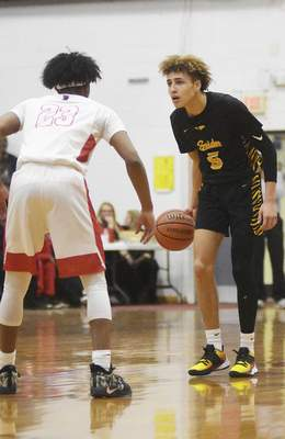 Katie Fyfe | The Journal Gazette  Snider junior Michael Eley comes down the court while Bishop Luers junior Naylon Thompson defends him during the second quarter at Bishop Luers High School on Friday.