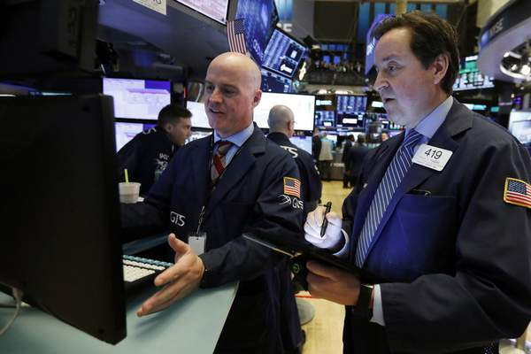 FILE - In this Feb. 6, 2020, file photo specialist John O'Hara, left, and trader Philip Powers work on the floor of the New York Stock Exchange. The U.S. stock market opens at 9:30 a.m. EST on Friday, Feb. 14. (AP Photo/Richard Drew, File)
