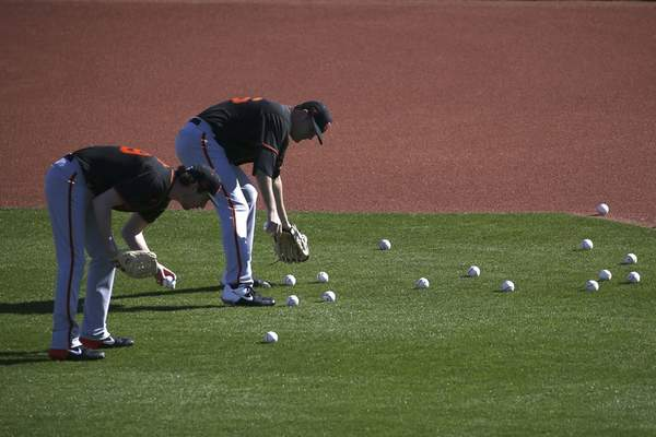 San Francisco Giants pitchers Jerry Blevins, left, and Andrew Triggs, right, pick up baseballs after a fielding drill during spring training baseball workouts for pitchers and catchers Wednesday, Feb. 12, 2020, in Scottsdale, Ariz. (AP Photo/Ross D. Franklin)