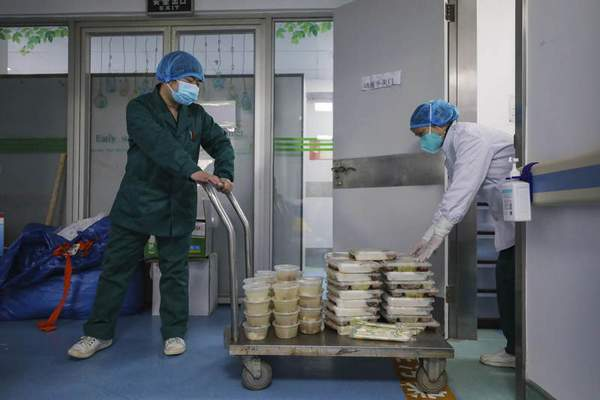 Workers deliver meals at the Jinyintan Hospital, designated for critical COVID-19 patients, in Wuhan in central China's Hubei province Thursday, Feb. 13, 2020. China on Thursday reported 254 new deaths and a spike in virus cases of 15,152, after the hardest-hit province of Hubei applied a new classification system that broadens the scope of diagnoses for the outbreak, which has spread to more than 20 countries. (Chinatopix Via AP)