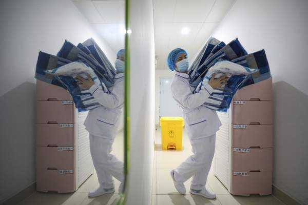 A worker prepares medical supplies at the Jinyintan Hospital, designated for critical COVID-19 patients, in Wuhan in central China's Hubei province Thursday, Feb. 13, 2020. China on Thursday reported 254 new deaths and a spike in virus cases of 15,152, after the hardest-hit province of Hubei applied a new classification system that broadens the scope of diagnoses for the outbreak, which has spread to more than 20 countries. (Chinatopix Via AP)