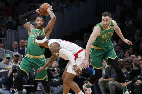Boston Celtics guard Marcus Smart (36) controls the ball against Los Angeles Clippers forward Marcus Morris Sr., center, as Celtics forward Gordon Hayward (20) moves downcourt in the first half of an NBA basketball game, Thursday, Feb. 13, 2020, in Boston. (AP Photo/Elise Amendola)