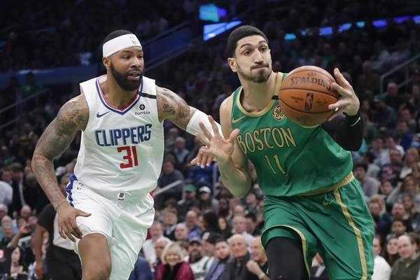Boston Celtics center Enes Kanter (11) goes to the hoop past Los Angeles Clippers forward Marcus Morris Sr. (31) in the first half of an NBA basketball game, Thursday, Feb. 13, 2020, in Boston. (AP Photo/Elise Amendola)