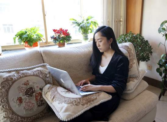 Associated Press photos Maggie Zhang, founder of a company in Beijing that organizes events for women, works on a laptop at her parents' home in the northwestern city of Zhangye. The virus outbreak means her Lunar New Year visit will last until March.