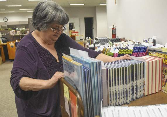 Patten checks to make sure that books are properly shelved at the Allen County Public Library's Technical Services building.