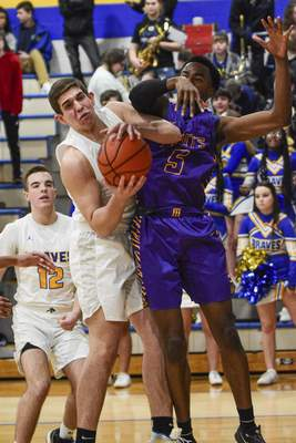 Mike Moore | The Journal Gazette  Blackhawk forward Jacob Boyer comes down with a rebound against Marion forward Jermaine Woods in the first quarter at Blackhawk Christian on Tuesday.