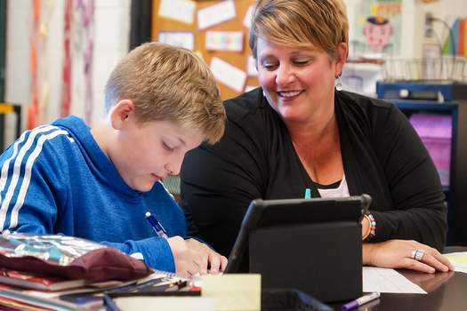 FILEA fifth-grade teacher at Leo Elementary School sits with a student in her classroom.