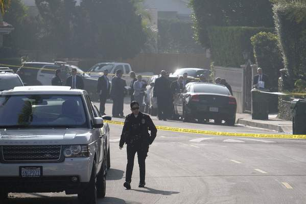 Police officers and investigators work outside a Hollywood Hills home where a fatal shooting occurred on Wednesday, Feb. 19, 2020, in Los Angeles. (AP Photo/Ringo H.W. Chiu)