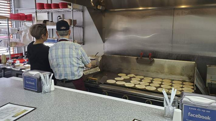 Owner Jesus Granados talks to an employee as perfectly arranged tortillas get warm on his griddles at Jeny's Tacos in Kendallville.