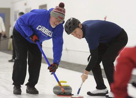 Photos by Katie Fyfe | The Journal Gazette Volunteer Mark DeWitt, left, and Tony King sweep in front of the stone at the Fort Wayne Curling Club on Wells Street this month. Every Sunday through March, the club hosts a program for those with special needs from 3 to 4:30 p.m.