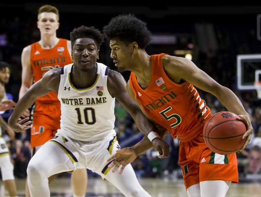 Miami's Harlond Beverly (5) drives in next to Notre Dame's Temple 'T.J.' Gibbs (10) during the first half of an NCAA college basketball game Sunday, Feb. 23, 2020, in South Bend, Ind. (AP Photo/Robert Franklin)