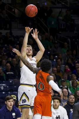 Notre Dame's Rex Pflueger, left, shoots a 3-pointer over Miami's Chris Lykes (0) during the second half of an NCAA college basketball game Sunday, Feb. 23, 2020, in South Bend, Ind. (AP Photo/Robert Franklin)
