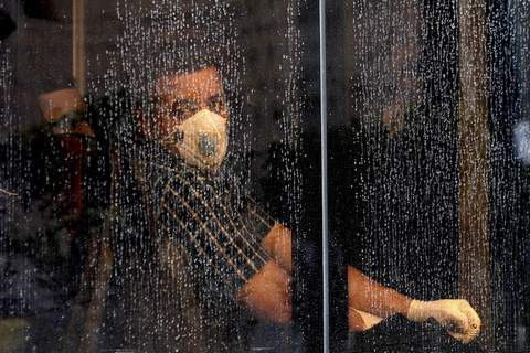 APTOPIX Iran Virus Outbreak A commuter looks through a water-stained window wearing a mask and gloves to help guard against the Coronavirus, on a public bus in downtown Tehran, Iran, Sunday, Feb. 23, 2020. (AP Photo/Ebrahim Noroozi) (Ebrahim Noroozi
