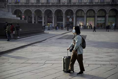 Italy China Europe Outbreak A woman wearing a sanitary mask pushes a trolley in Duomo square, Milan, Italy, Sunday, Feb. 23, 2020.  (AP Photo/Luca Bruno) (Luca Bruno