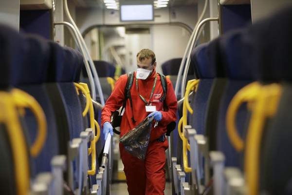 A cleaner sanitizes a wagon on a regional train, at the Garibaldi train station in Milan, Italy, Friday, Feb. 28, 2020.  (AP Photo/Luca Bruno)