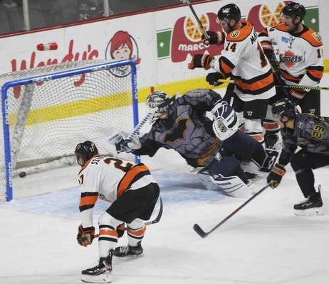 Justin A. Cohn | The Journal Gazette Komets forward Shawn Szydlowski, left watches as his first-period shot goes in Friday night at the Huntington Center, and Walleye goalie Billy Christopoulos reacts to late in Toledo, Ohio.