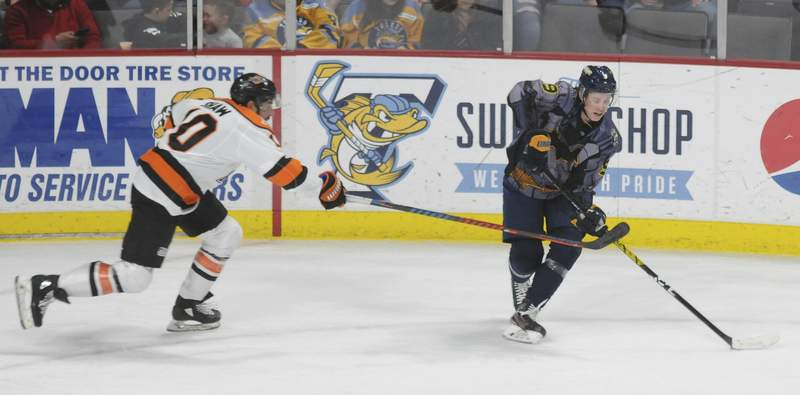Justin A. Cohn | The Journal Gazette Komets forward Brady Shaw, left, chases the Toledo Walleye's Troy Loggins at the Huntington Center in Toledo, Ohio, on Friday night.