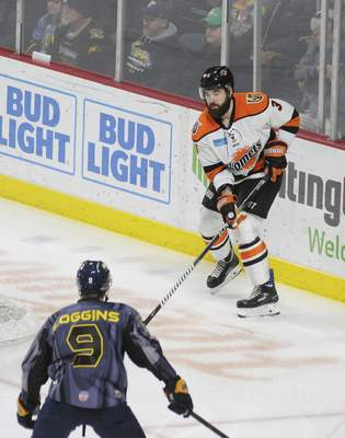 Justin A. Cohn | The Journal Gazette  Komets defenseman Chase Stewart, top, looks to pass the puck as the Toledo Walleye's Troy Loggins defends Friday at the Huntington Center in Toledo, Ohio.