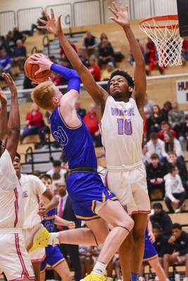 Mike Moore | The Journal Gazette Homestead forward Luke Goode scores over Wayne forward Christian Flanagan in the second period of the IHSAA Class 4A Sectional Tournament at Huntington North High School on Tuesday.