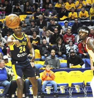 Justin A. Cohn | The Journal Gazette  The Mad Ants' Alize Johnson, left, passes the ball as College Park's Kenny Gabriel looks on Friday at Memorial Coliseum.