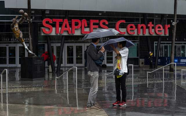 Tourist stand under umbrellas in rain outside Staples Center, home to hockey's Los Angeles Kings and basketball's Los Angeles Lakers, Clippers and Sparks, in Los Angeles on Thursday, March 12, 2020. Officials have banned large gatherings and events in Los Angeles to try to stop the spread of the new coronavirus. (AP Photo/Damian Dovarganes)