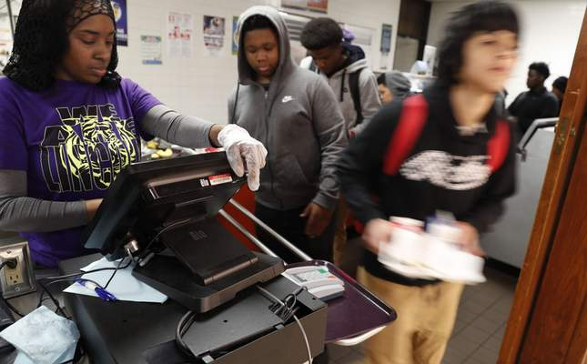Associated Press photos Students line up in the cafeteria for lunch Friday at Lincoln High School in Dallas. The cafeteria and others in the Dallas Independent School District will provide lunches to students during the upcoming school closure.