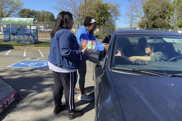 Staffers at Florin Elementary School in Sacramento, Calif., hand out food to students and parents driving in Tuesday, after their facility closed in response to the coronavirus outbreak.