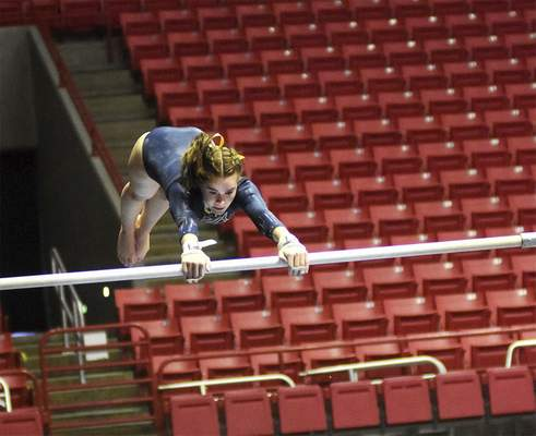 Katie Fyfe | The Journal Gazette  Bishop Dwenger junior Emma Doyle does the uneven parallel bars during the 48th Annual Gymnastics State Finals at Worthen Arenain Muncie on Saturday.