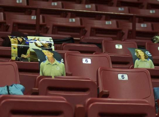 Katie Fyfe | The Journal Gazette  Printed photos of people who could not attend are placed on empty chairs during the 48th Annual Gymnastics State Finals at the Worthen Arenain Muncie on Saturday.