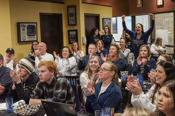 Mike Moore | The Journal Gazette Family and friends of Bishop Dwenger gymnasts who were unable to attend the State Competition in Muncie on Saturday cheer for their team during a watch party held at Mitchell's Sports Bar & Grill.