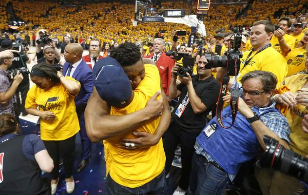 FILE - In this April 27, 2018, file photo, Utah Jazz guard Donovan Mitchell, center, hugs his father as he walks off the court following Game 6 of an NBA basketball first-round playoff series in Salt Lake City. Mitchell Sr., who works for the New York Mets, has tested negative for the coronavirus. Mitchell Sr. is the Mets' director of player relations and community outreach. The younger Mitchell confirmed Thursday, March 12, 2020, he tested positive for the virus after Jazz teammate Rudy Gobert became the first NBA player to test positive, with Gobert's result prompting the league to suspend the season. (AP Photo/Rick Bowmer, File)