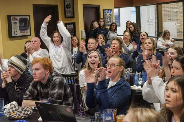 Mike Moore   The Journal Gazette Family and friends of Bishop Dwenger gymnasts who were unable to attend the state finals in Muncie on Saturday cheer at Mitchell's Sports Bar & Grill.