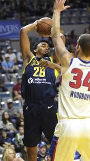 Katie Fyfe | The Journal Gazette  Mad Ants forward Ben Moore takes a shot while Grand Rapids' Adam Woodbury tries to block him at Memorial Coliseum,