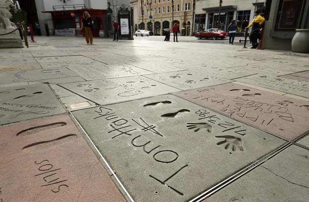 The cement inscription of actor Tom Hanks sits in the nearly empty forecourt of the TCL Chinese Theatre, Thursday, March 12, 2020, in the Hollywood section of Los Angeles. (AP Photo/Chris Pizzello)