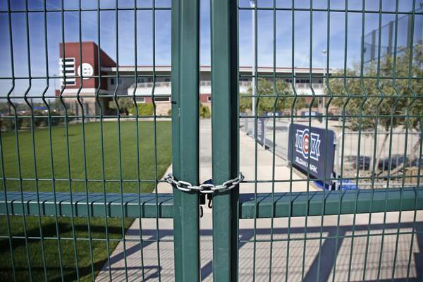 Associated Press A gate at the Chicago Cubs practice facility in Mesa, Ariz., is closed and locked Monday.