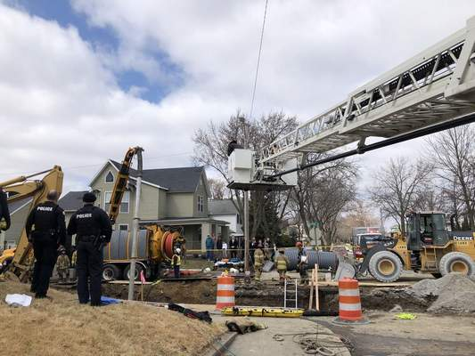 Katie Fyfe | The Journal Gazette Fort Wayne Firefighters try to free a man that was buried in loose gravel today at Huffman Avenue and Franklin Street.