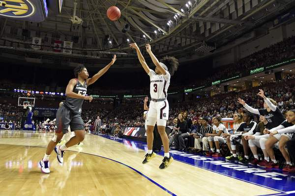 South Carolina's Destanni Henderson, right, shoots a three-point shot while defended by Arkansas' Rokia Doumbia during the second half of a semifinal match at the Southeastern Conference women's NCAA college basketball tournament in Greenville, S.C., Saturday, March 7, 2020. (AP Photo/Richard Shiro)