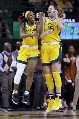 Baylor guard Te'a Cooper, left and forward Lauren Cox, right, jump at the end of the first quarter of the team's NCAA college basketball game against Texas on Thursday, March 5, 2020, in Waco, Texas. (AP Photo/Ray Carlin)