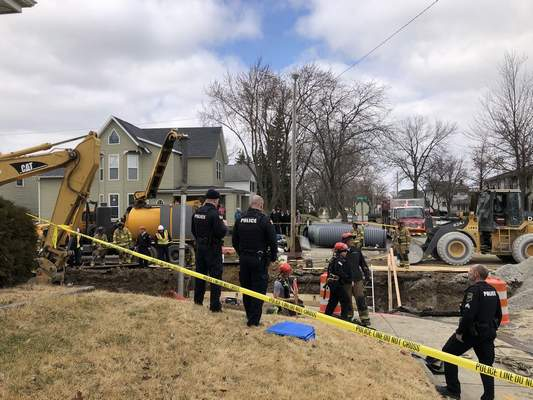 Katie Fyfe   The Journal Gazette Emergency crews respond to a man buried in a trench at the intersection of Franklin Avenue and Huffman Street, Tuesday afternoon.