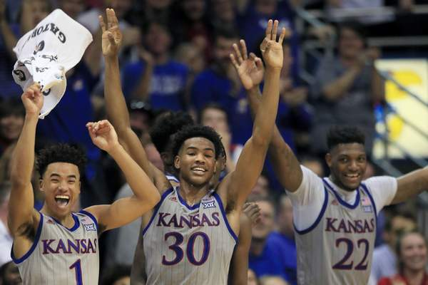 FILE - In this Nov. 15, 2019, file photo, Kansas guards Devon Dotson (1), Ochai Agbaji (30) and forward Silvio De Sousa (22) celebrate a teammate's three-point basket during the second half of an NCAA college basketball game against Monmouth in Lawrence, Kan.(AP Photo/Orlin Wagner, File)