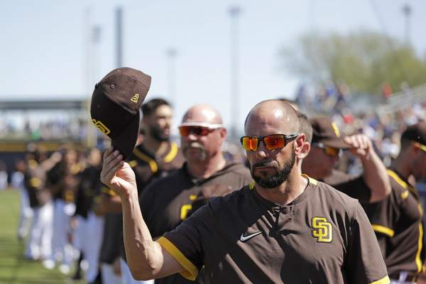 San Diego Padres manager Jayce Tingler tips his cap at the conclusion of the national anthem before a spring training baseball game against the Los Angeles Dodgers, Monday, March 9, 2020, in Peoria, Ariz. (AP Photo/Elaine Thompson)