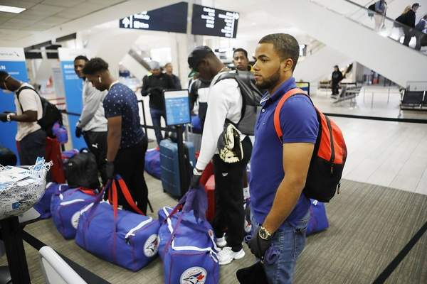Toronto Blue Jays minor league baseball player Steward Berroa, right, prepares to fly home along with his teammates from the Dominican Republic at the Tampa International Airport in Tampa, Florida on Sunday, March 15, 2020. Flight schedules for departures and arrivals remain normal during the coronavirus pandemic. (Octavio Jones/Tampa Bay Times via AP)