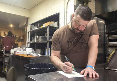 Michelle Davies | The Journal Gazette Kevin Cook checks an order form in the kitchen of the pop up market, Water Street Mercantile, inside Don Hall's Gashouse Thursday morning. The market is open 11am to 7pm daily and offers both groceries and a full menu carryout service.