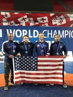 Courtesy photos Gralan Early, left, and his teammates hold an American flag during the Veterans World Championships in October in Tbilisi, Georgia.