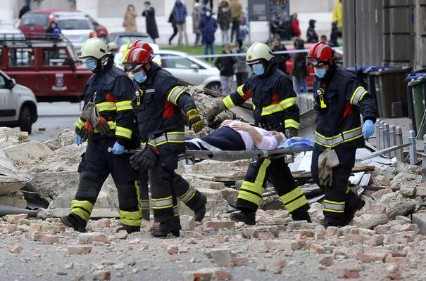 Associated Press Firefighters carry a person on a stretcher Sunday after an earthquake in Zagreb, Croatia.